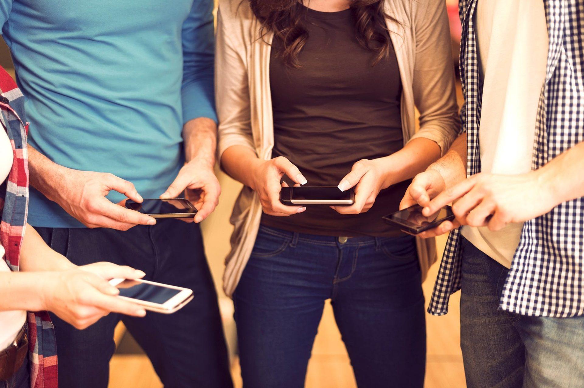 four people looking at social media on phones