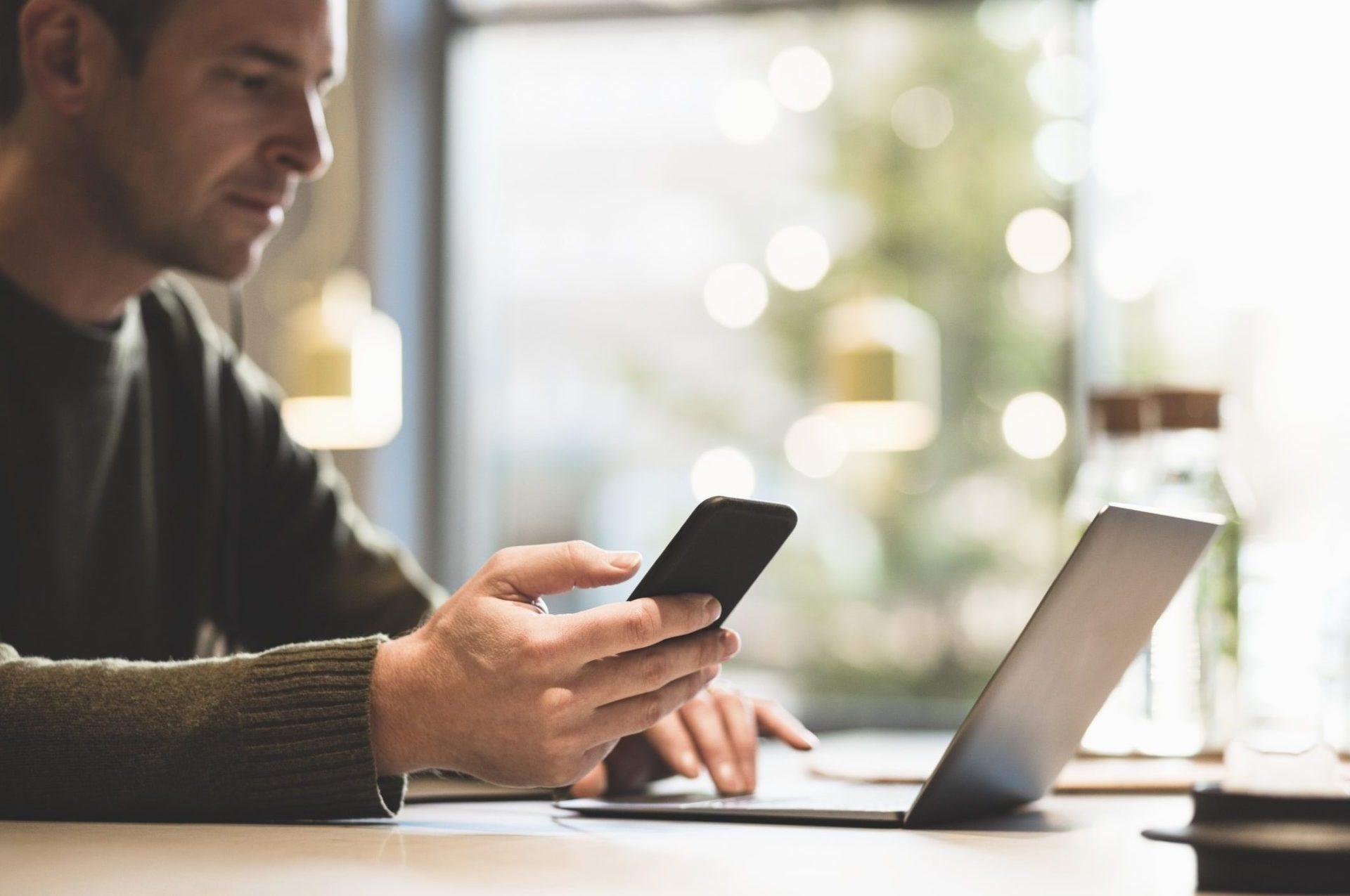 man looking at phone and computer