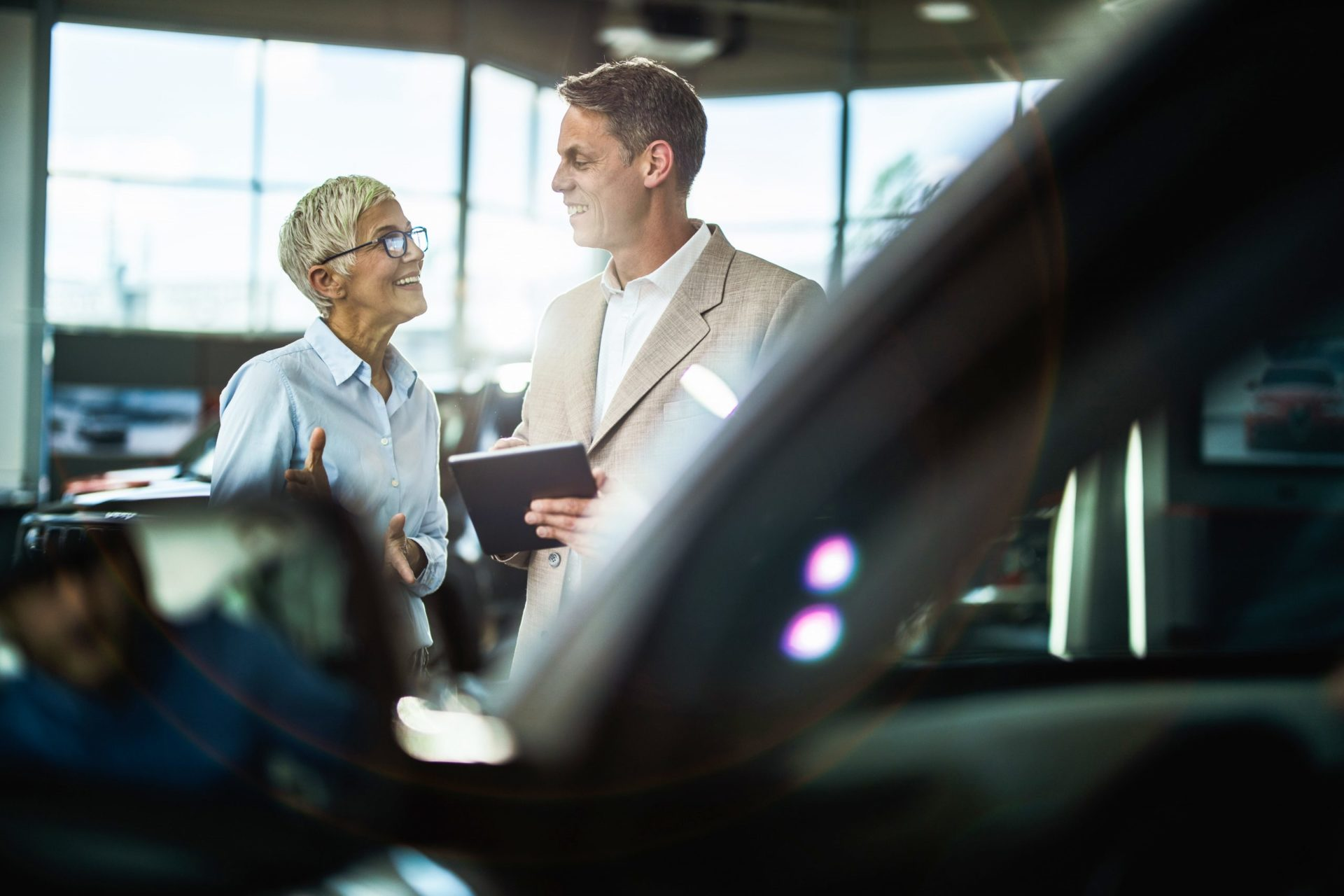car buyer and salesperson shaking hands in a dealership showroom