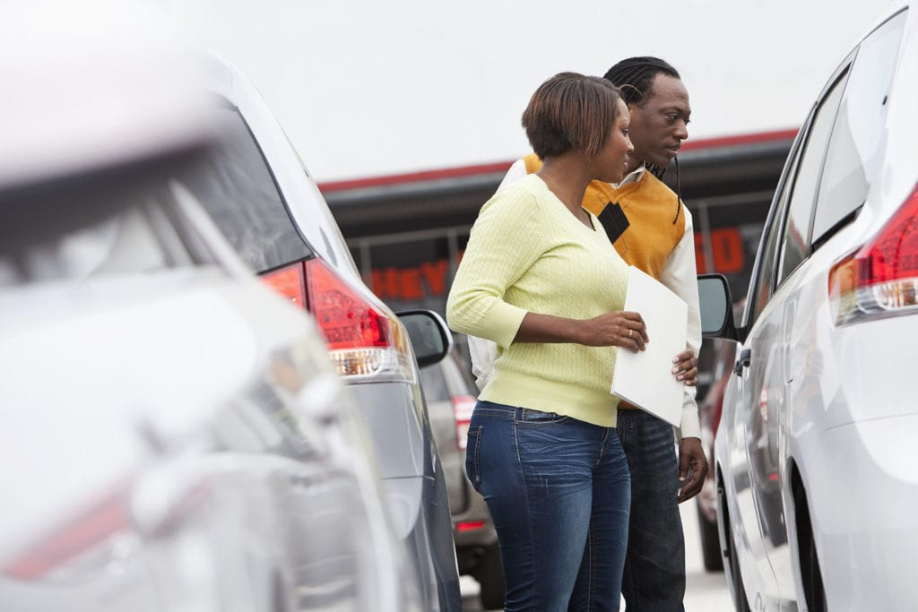 Couple shopping for pre-owned car at dealership