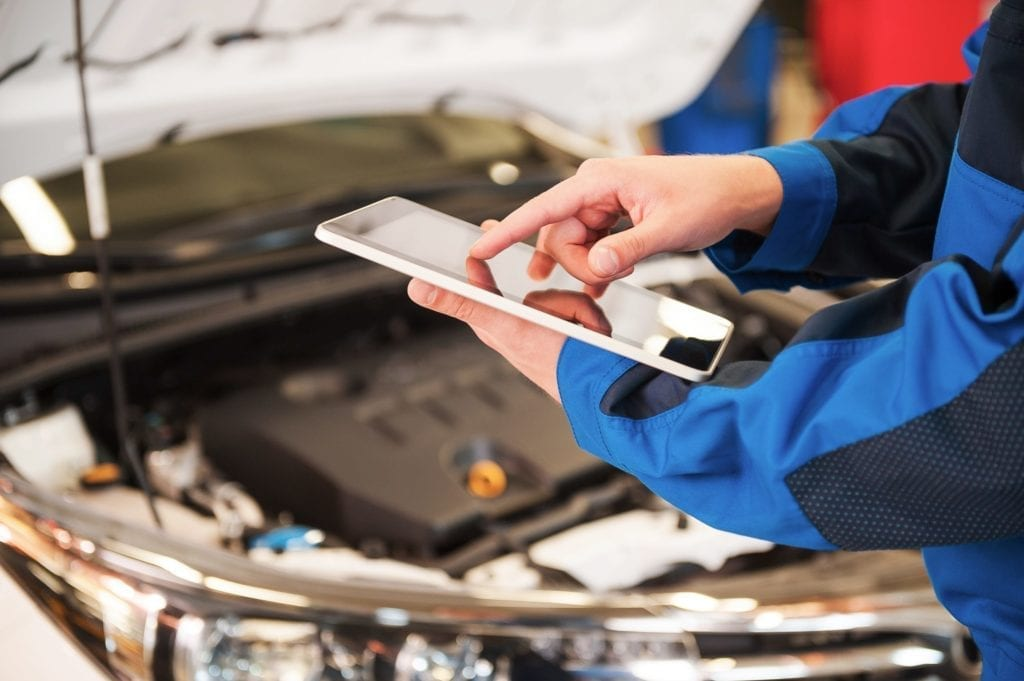 Close-up of man in uniform working on digital tablet while standing in front of car hood in vehicle service center