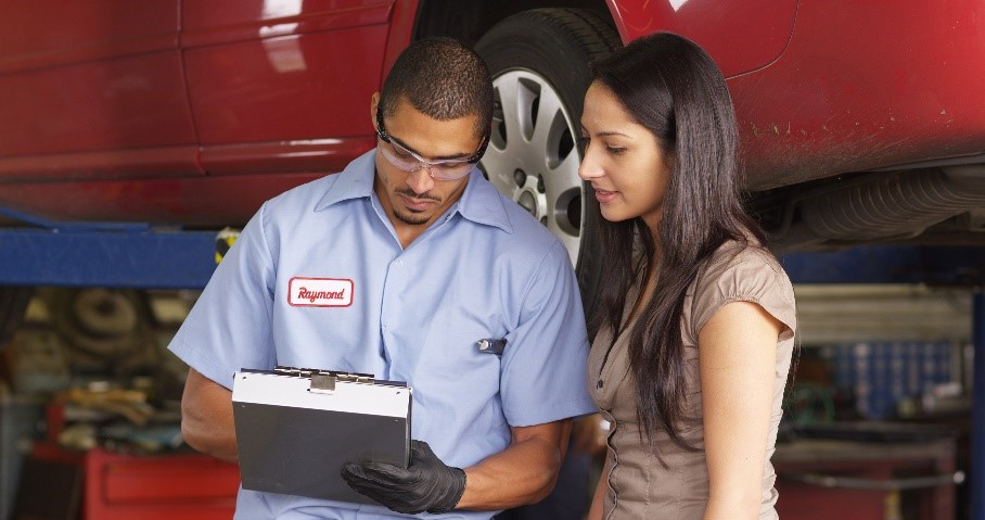 Vehicle service professional and a dealership customer looking over paperwork in a service bay