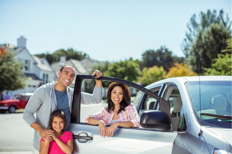 A family in front of the new car that has been delivered to their driveway
