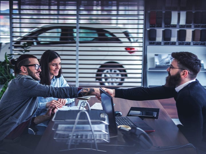 two car buyers and a dealership salesperson closing a deal