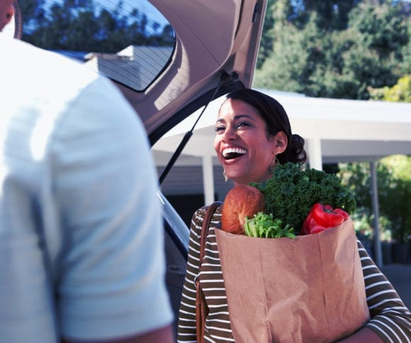 couple taking groceries out of the trunk of an SUV